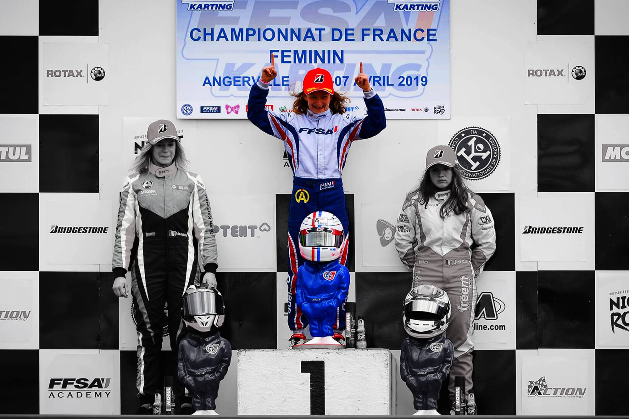 Doriane Pin, French Karting Champion 2019 raising her arms on the first step of the podium